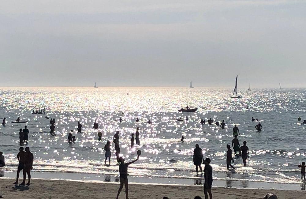 Baigneurs au bord de la mer au soleil couchant