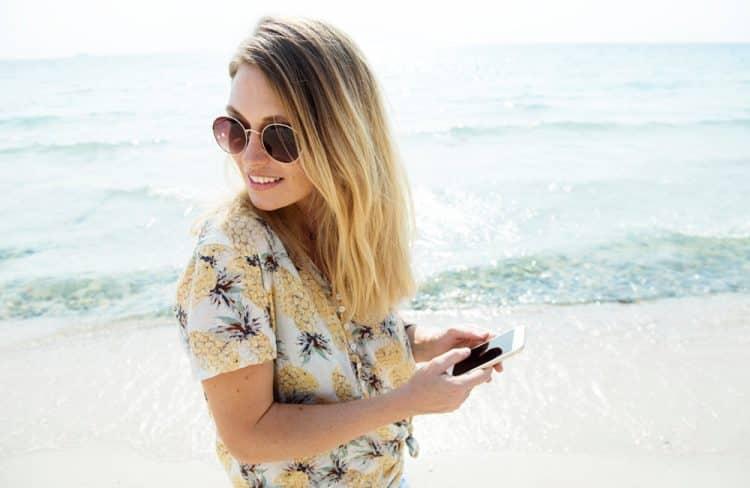 Femme utilisant son téléphone à la plage