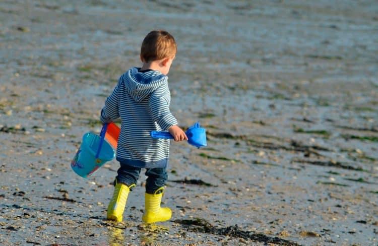 Enfant sur la plage avec pelle et râteau